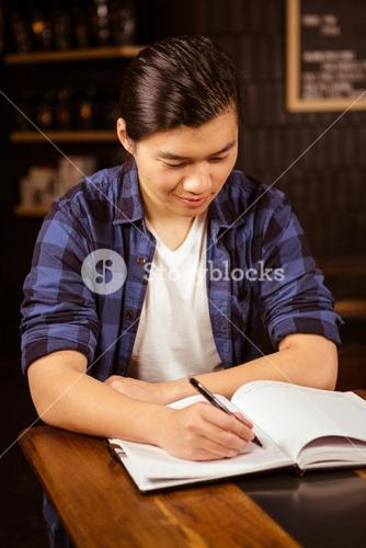 Hipster man writing on a planner