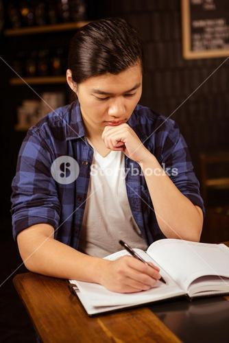 Hipster man writing on planner