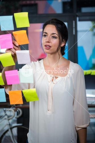 Businesswoman moving sticky notes