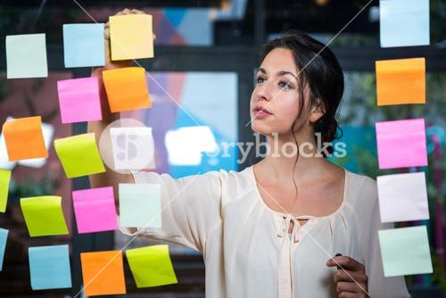 Businesswoman moving a post-it