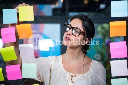 Businesswoman writing on sticky note