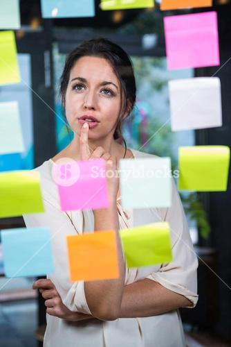 Businesswoman looking at sticky note