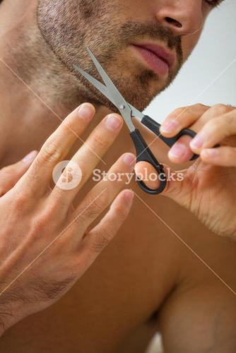 Young man cutting beard with scissor