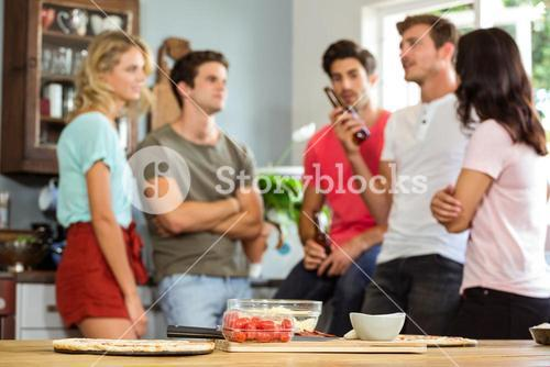 Group of young friends talking in kitchen