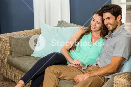 Young couple sitting together in sofa