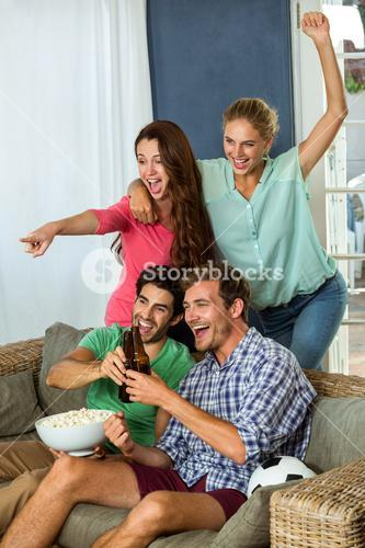 Excited friends watching football match on television at home