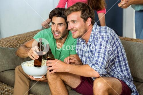 Friends watching football match on television at home