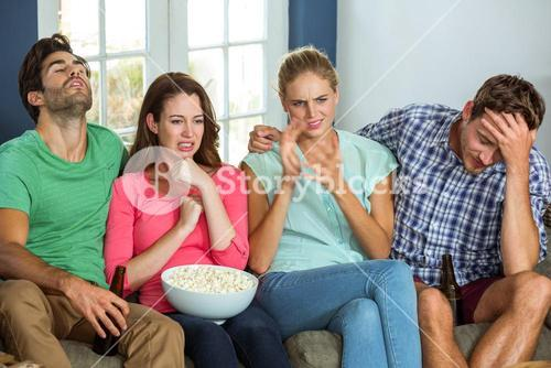 Unhappy friends watching sports match on television