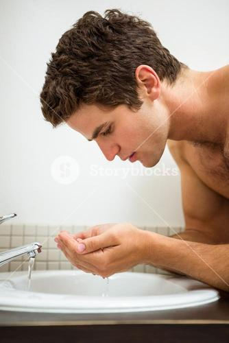 Man washing his face in the bathroom