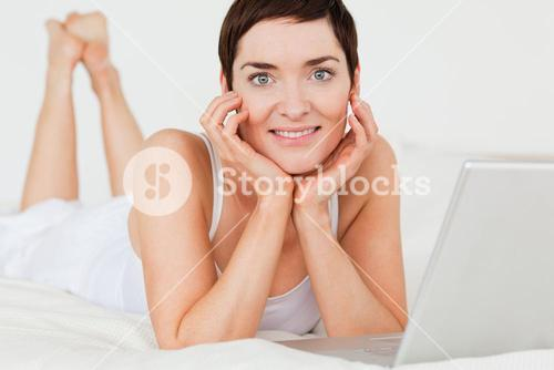 Close up of a woman posing with a laptop