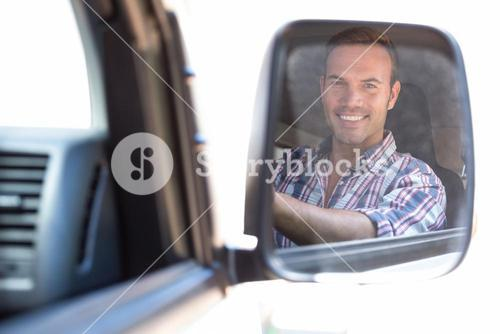 Young man driving with his reflection in rear view mirror