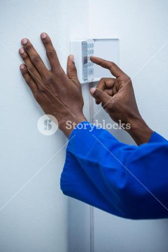 Hand touching home security keypad