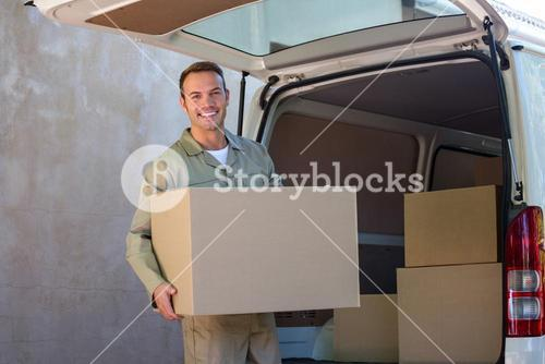 Happy delivery man carrying a cardboard box