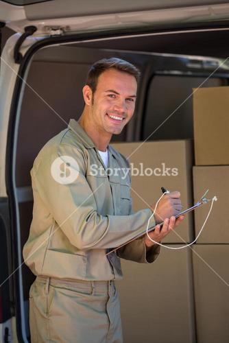 Happy delivery man writing on a clipboard