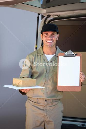 Happy delivery man holding cardboard box and clipboard