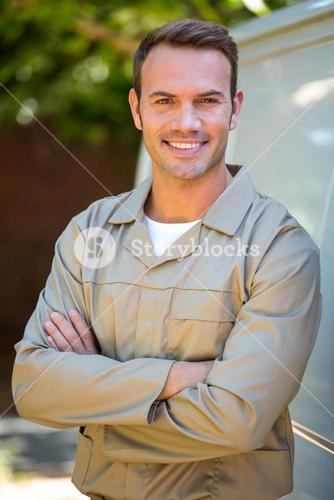 Confident delivery man standing with arms crossed