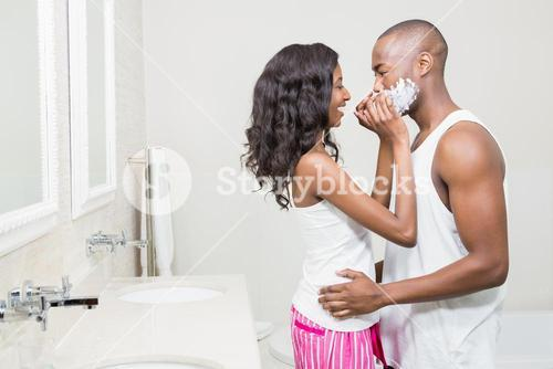 Young woman applying shaving cream on young mans face