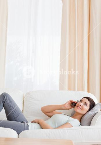 Portrait of a brunette calling while lying on a sofa