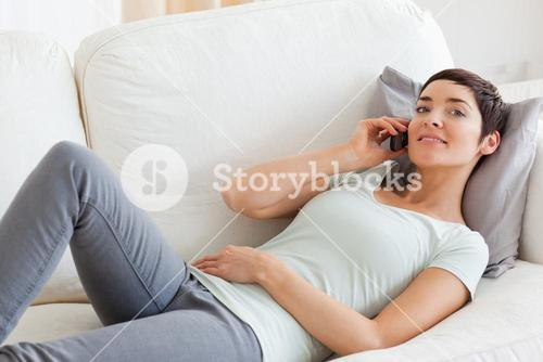 Close up of a cute brunette calling while lying on a sofa