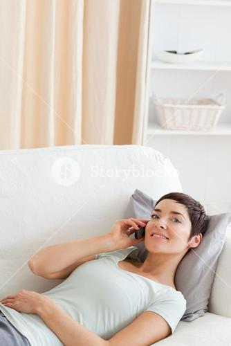 Portrait of a cute brunette calling while lying on a sofa