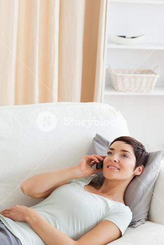 Portrait of a young brunette calling while lying on a sofa