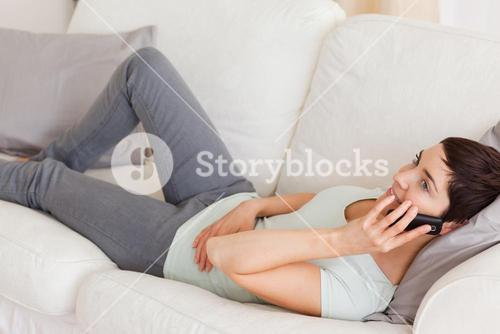 Calm brunette calling while lying on a sofa