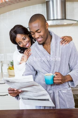 Young couple reading newspaper