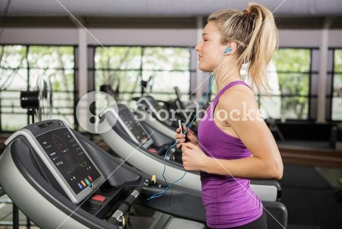 Woman listening to music while jogging on the thread mill