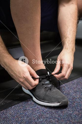 Man tying up his shoe lace