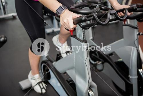 Woman working out on exercise bike at spinning class