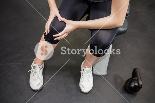 Woman with an injured knee sitting in gym