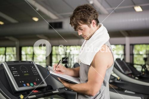 Gym instructor writing on clipboard