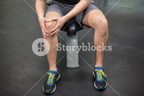 Man with an injured knee sitting in gym