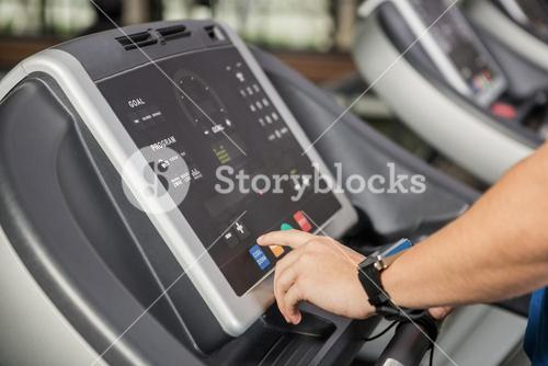 Hand pressing a button on the console display of a treadmill