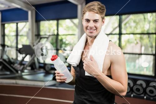 Man holding a water bottle at gym