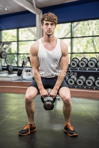 Determined man lifting kettle bells