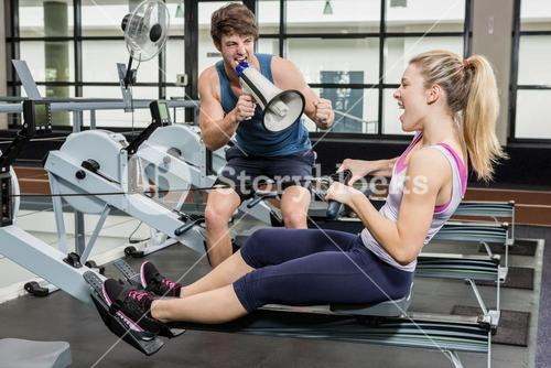Trainer yelling through a megaphone while woman on rowing machine
