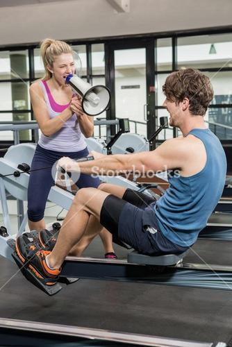 Trainer yelling through a megaphone while man on rowing machine