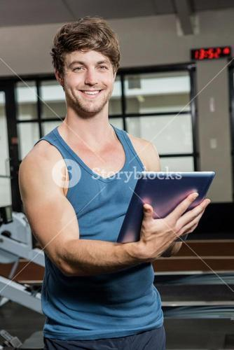 Portrait of gym trainer using a digital tablet