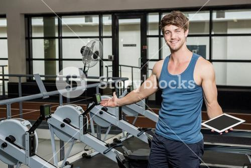 Happy gym trainer holding a digital tablet