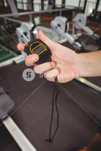 Hand of a trainer holding a stopwatch