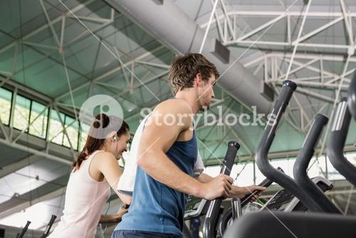 Beautiful woman and man exercising on the elliptical machine
