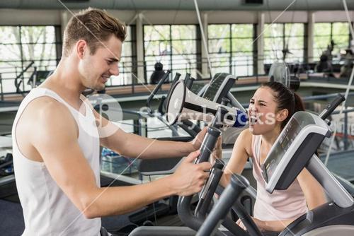 Trainer yelling through a megaphone while man exercising on elliptical machine