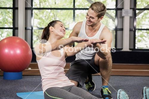 Trainer motivating a woman while doing crunches