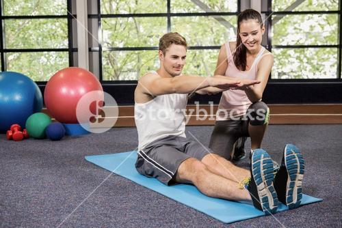 Trainer assisting man with abdominal crunches