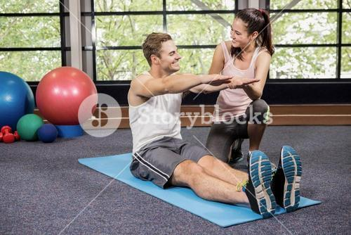 Trainer motivating a man while doing crunches