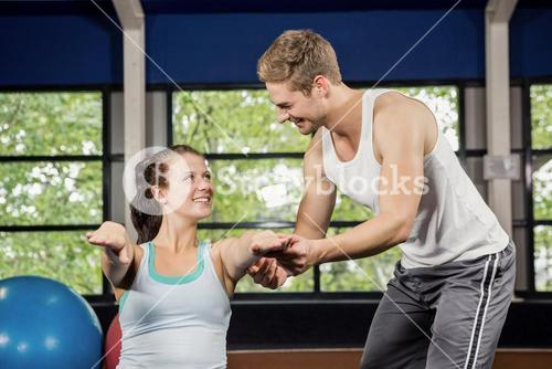 Trainer assisting woman with abdominal crunches