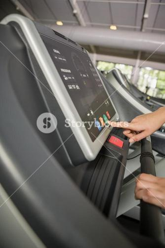 Hand of a person setting control panel of treadmill