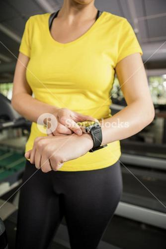 Mid section of woman using smart watch on treadmill