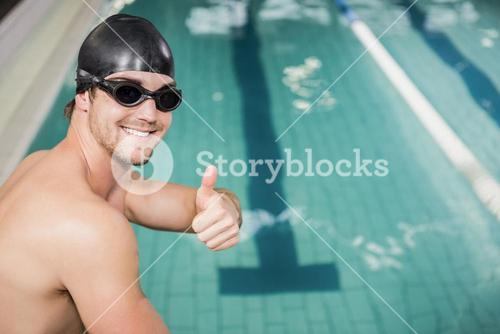 Swimmer gesturing thumbs up by the pool
